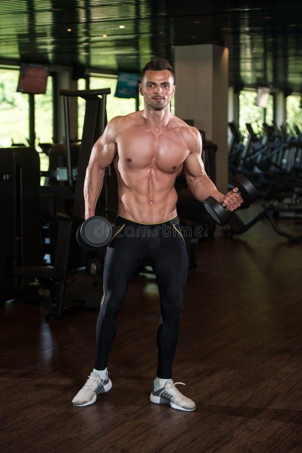 Homem novo que faz o exercício para o bíceps com pesos fotografia de stock royalty free