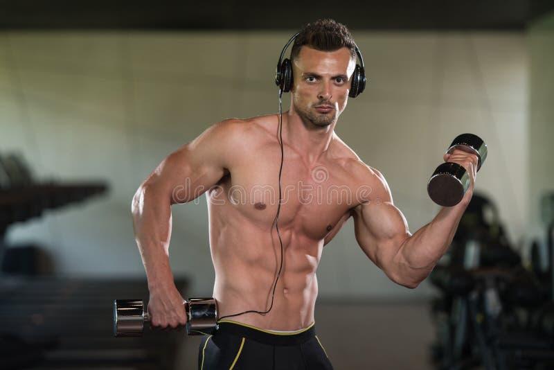 Homem novo que faz o exercício para o bíceps com pesos foto de stock