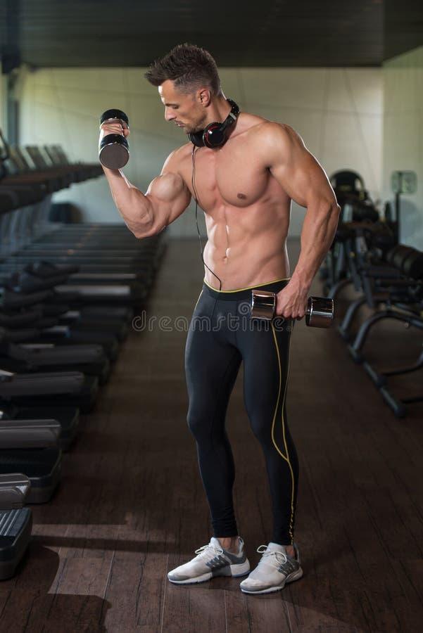 Homem novo que faz o exercício para o bíceps com pesos fotos de stock