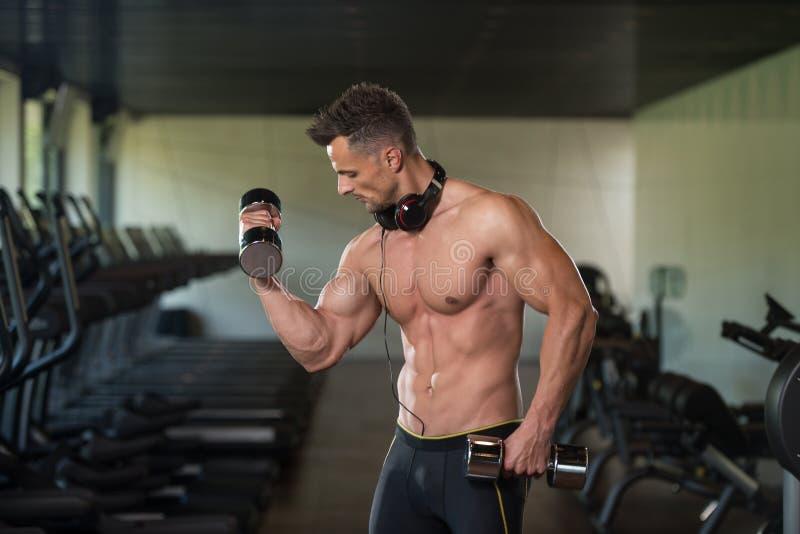 Homem novo que faz o exercício para o bíceps com pesos imagens de stock