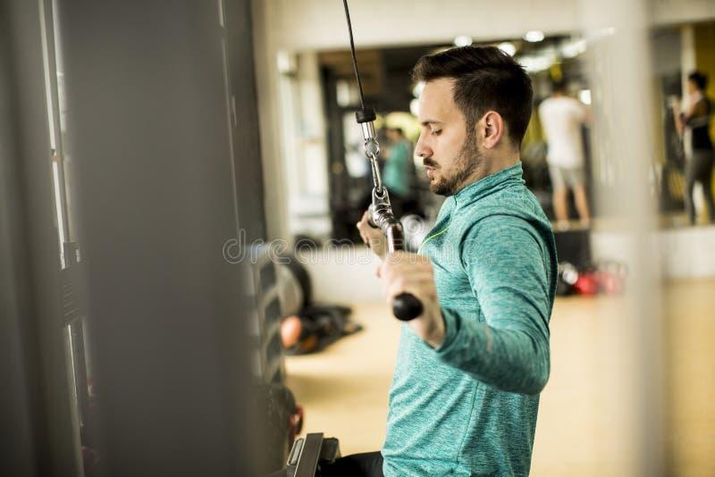 Homem novo que faz o exercício para o tríceps no gym fotografia de stock