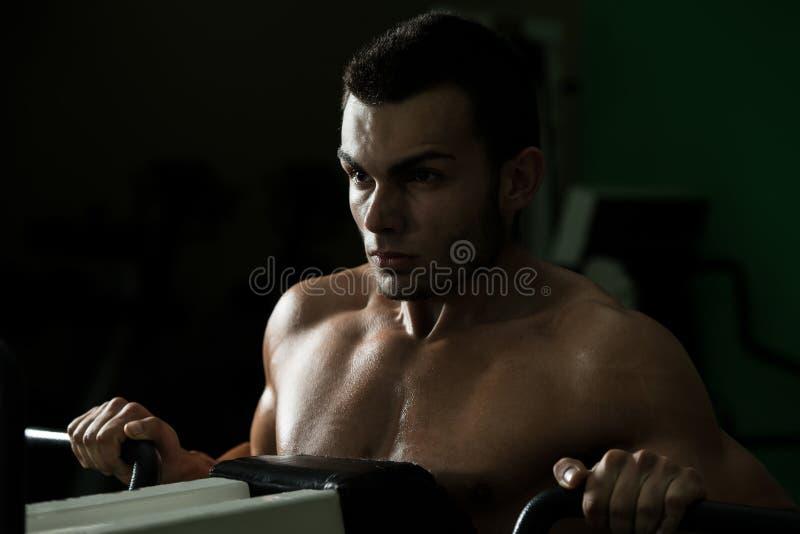 Homem novo que faz o exercício pesado para a parte traseira fotos de stock