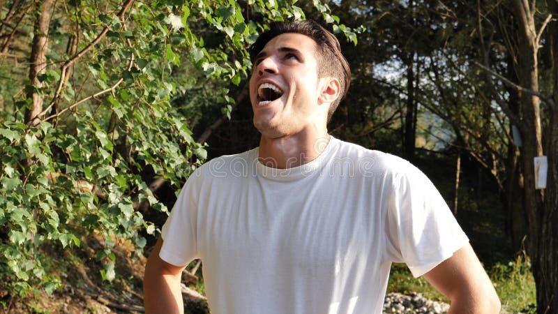 Homem novo que faz o riso mau, exterior na natureza fotos de stock royalty free