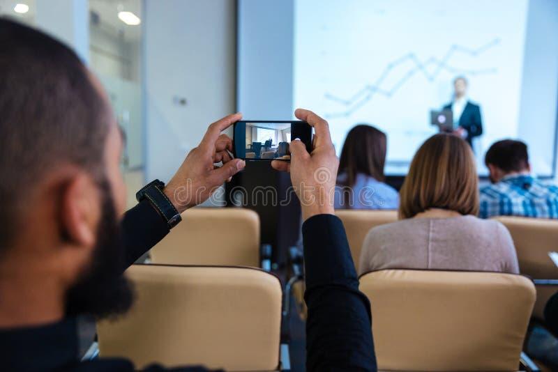 Homem novo que faz o vídeo com o smartphone na conferência de negócio fotos de stock royalty free