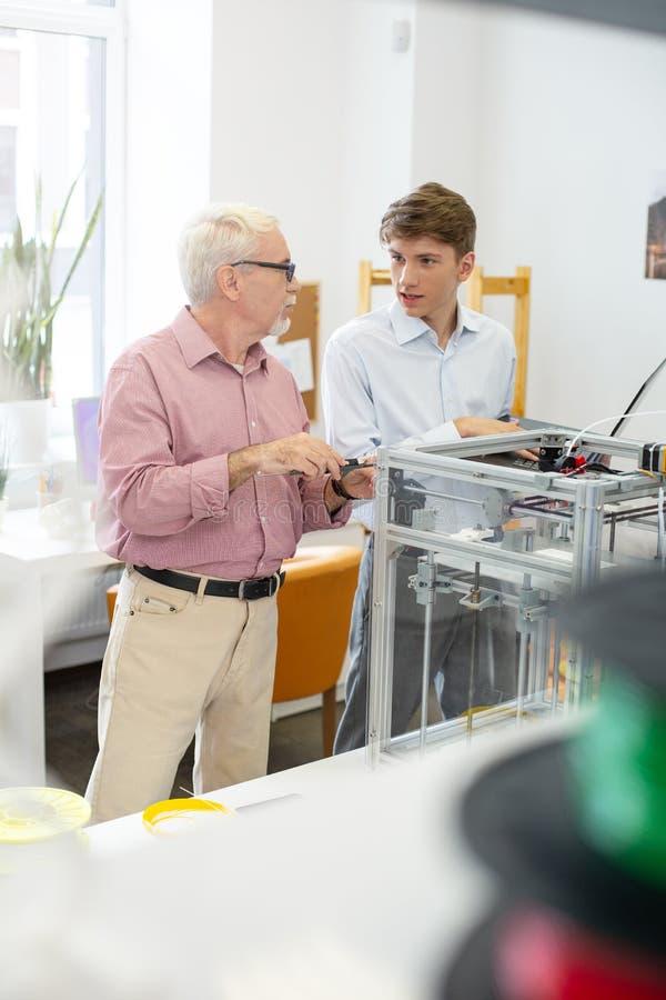 Homem novo que faz perguntas do supervisor sobre a impressão 3D imagens de stock