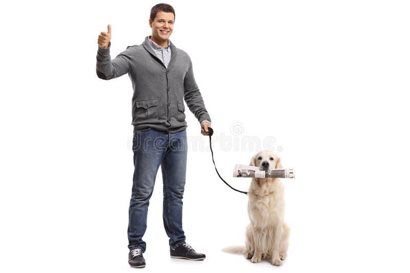 Homem novo que faz um polegar acima do sinal e um labrador retriever com a fotos de stock