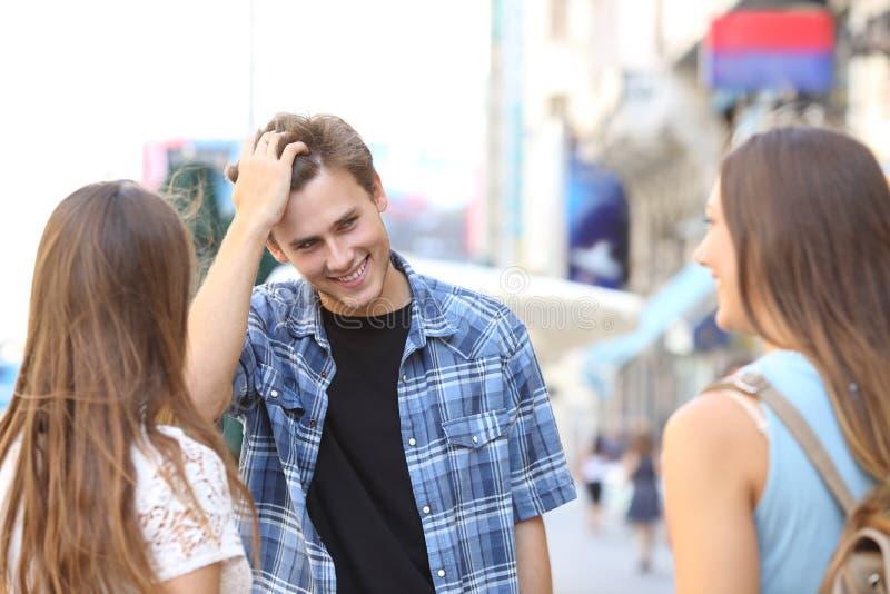 Homem novo que flerta com duas meninas foto de stock royalty free