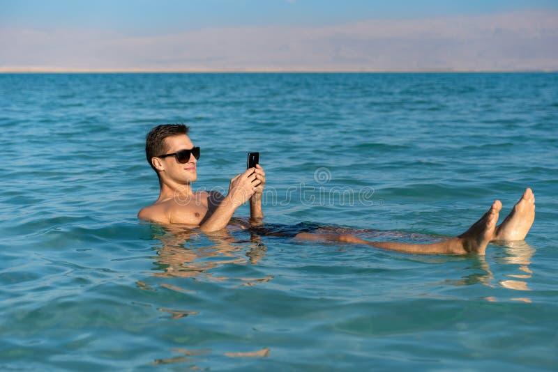 Homem novo que flutua na superfície da água do Mar Morto e que usa seu smartphone imagem de stock