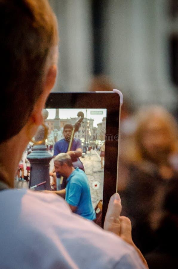 Homem novo que fotografa alguns músicos com sua tabuleta na praça Navona em Roma em julho de 2013 Italy imagens de stock royalty free