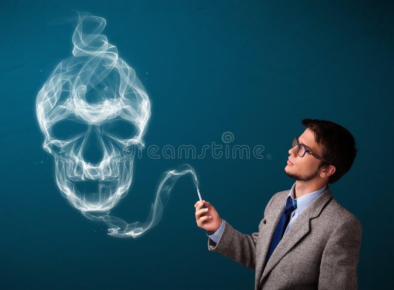 Homem novo que fuma o cigarro perigoso com fumo tóxico do crânio imagem de stock