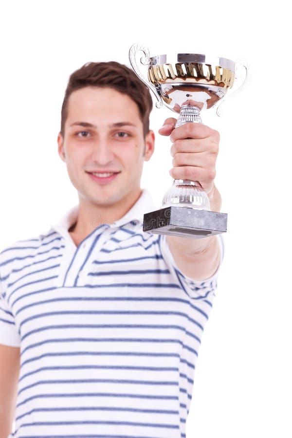 Homem novo que ganha o primeiro troféu do lugar imagem de stock royalty free