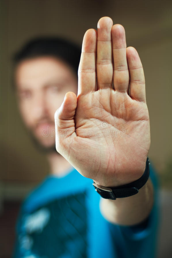 Homem novo que gesticula o batente com sua mão foto de stock