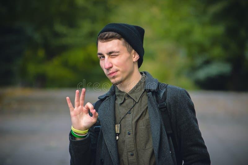 Homem novo que gesticula o sinal e piscadelas APROVADOS contra o fundo cinzento fotografia de stock