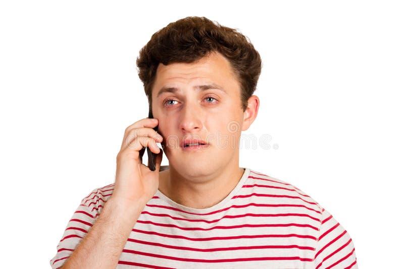 Homem novo que grita sobre as más notícias que está recebendo em seu telefone homem emocional isolado no fundo branco fotos de stock royalty free