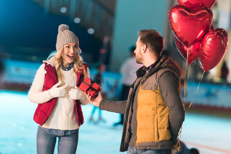 homem novo que guarda balões dados forma coração e que apresenta a caixa de presente à amiga entusiasmado fotografia de stock royalty free