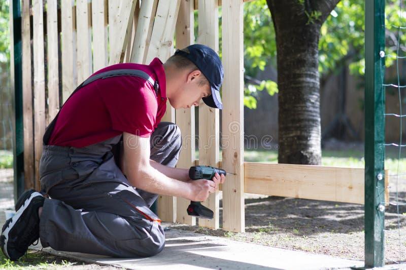 Homem novo que guarda a broca-movimenta??o O carpinteiro trabalha com plaina el?trica imagem de stock royalty free