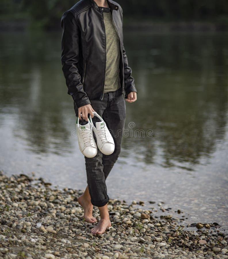 Homem novo que guarda com os pés descalços um par de Adidas Stan Smith imagem de stock royalty free