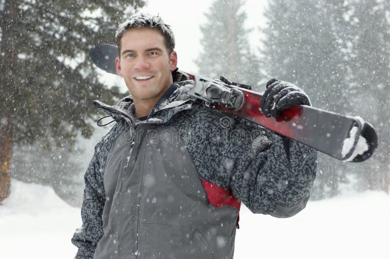 Homem novo que guarda esquis na neve fotos de stock