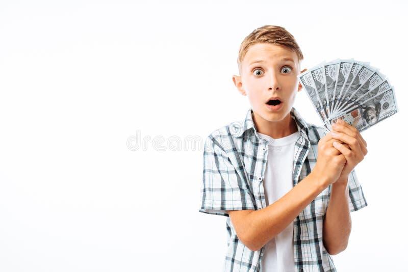 Homem novo que guarda muitas cem notas de dólar, indivíduo adolescente chocado por muito dinheiro, no estúdio no fundo branco imagens de stock