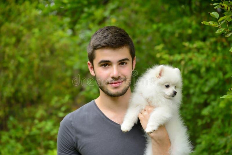 Homem novo que guarda o cachorrinho alemão do spitz foto de stock royalty free