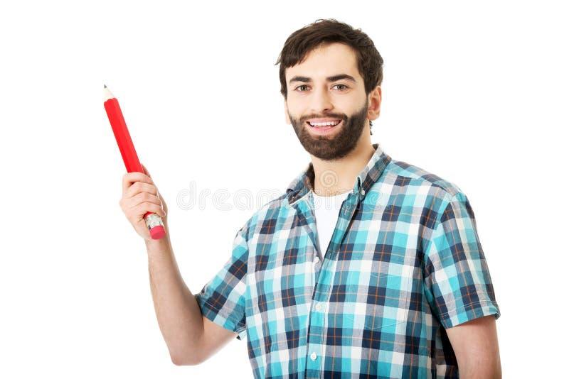 Homem novo que guarda o lápis vermelho grande foto de stock royalty free
