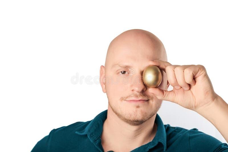 Homem novo que guarda o ovo dourado à câmera, sentindo segura fotografia de stock