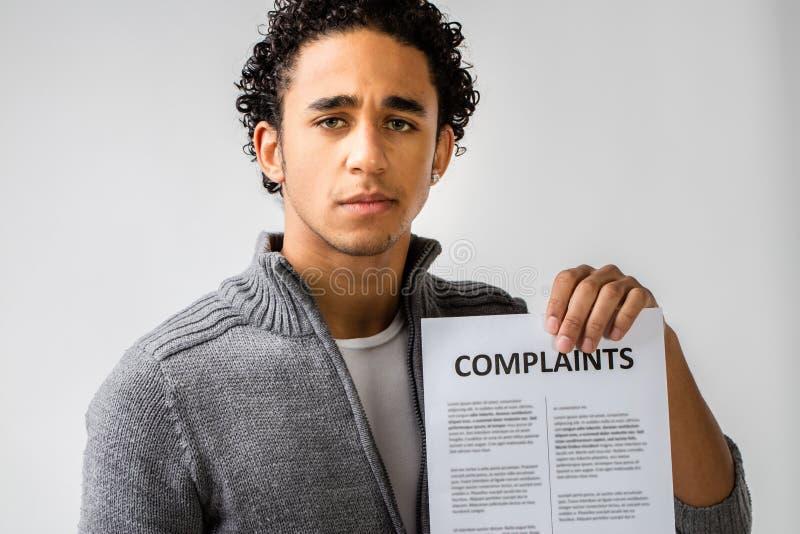 Homem novo que guarda o relatório das queixas imagens de stock