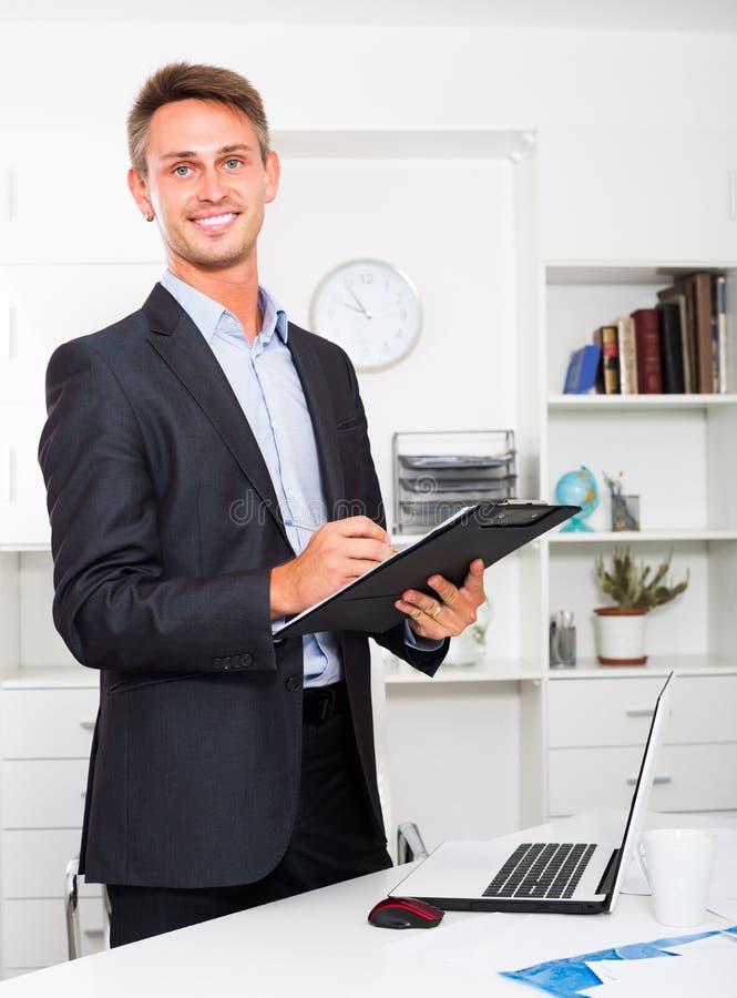 Homem novo que guarda a prancheta no escritório imagens de stock