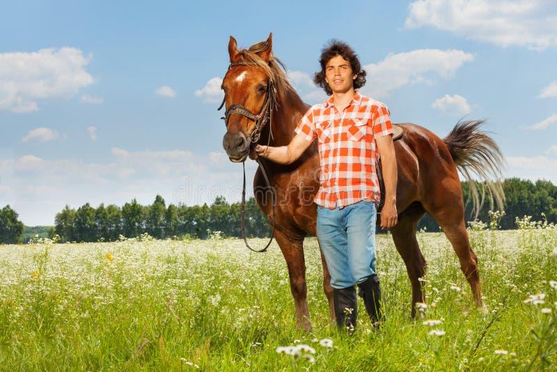 Homem novo que guarda seu cavalo marrom por um freio fotos de stock
