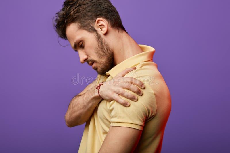 Homem novo que guarda seu ombro e que olha para baixo fotos de stock