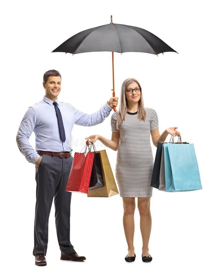 Homem novo que guarda um guarda-chuva sobre uma jovem mulher com sacos de compras imagem de stock