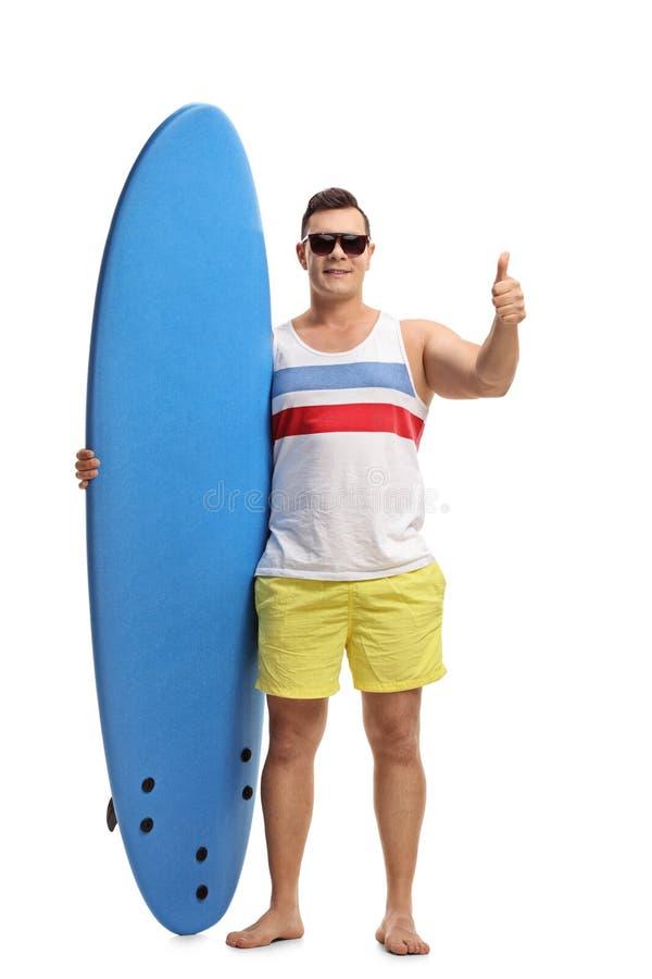 Homem novo que guarda uma prancha e que faz um polegar acima do gesto imagens de stock royalty free