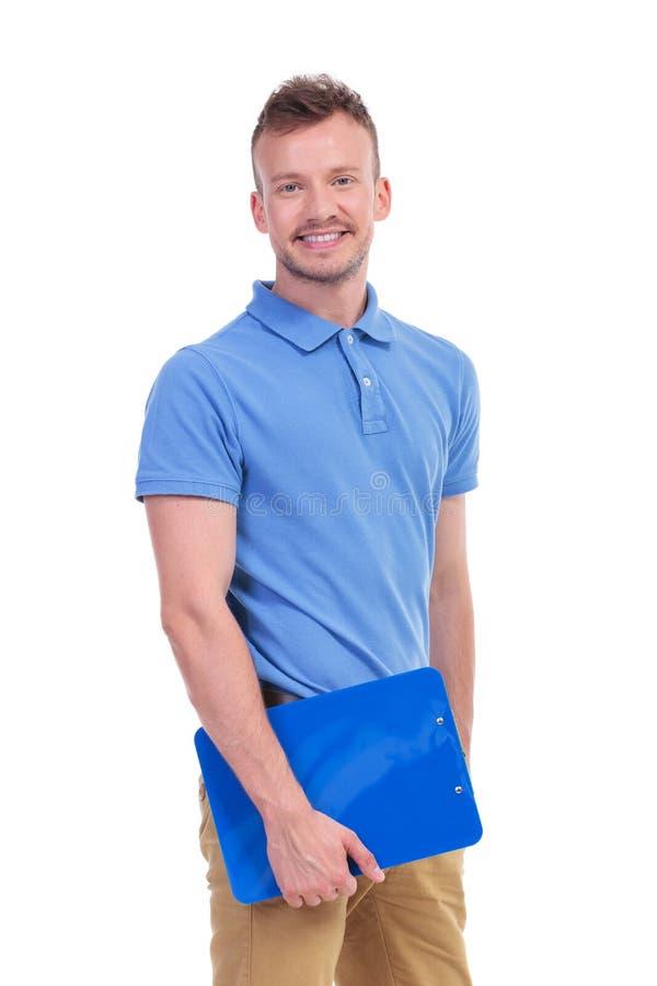 Homem novo que guarda uma prancheta fotografia de stock