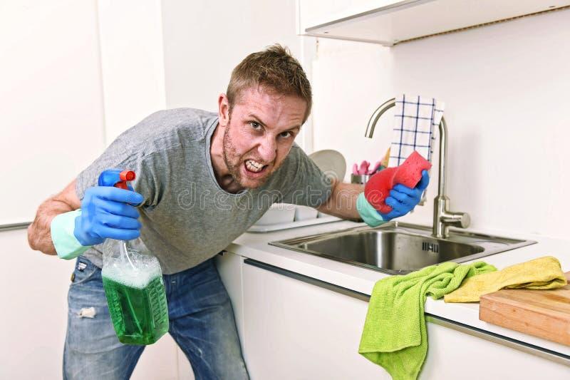 Homem novo que guardam o pulverizador detergente da limpeza e esponja que lava irritado limpo da cozinha home no esforço fotos de stock