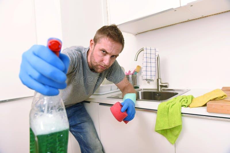 Homem novo que guardam o pulverizador detergente da limpeza e esponja que lava irritado limpo da cozinha home no esforço imagem de stock