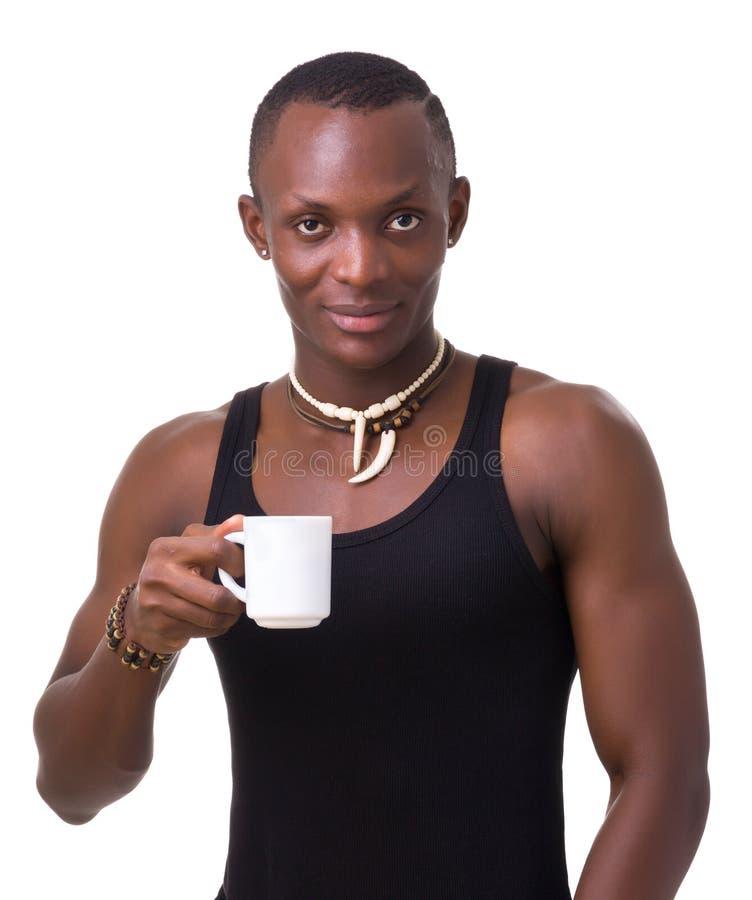 Homem novo que guardara uma chávena de café fotografia de stock