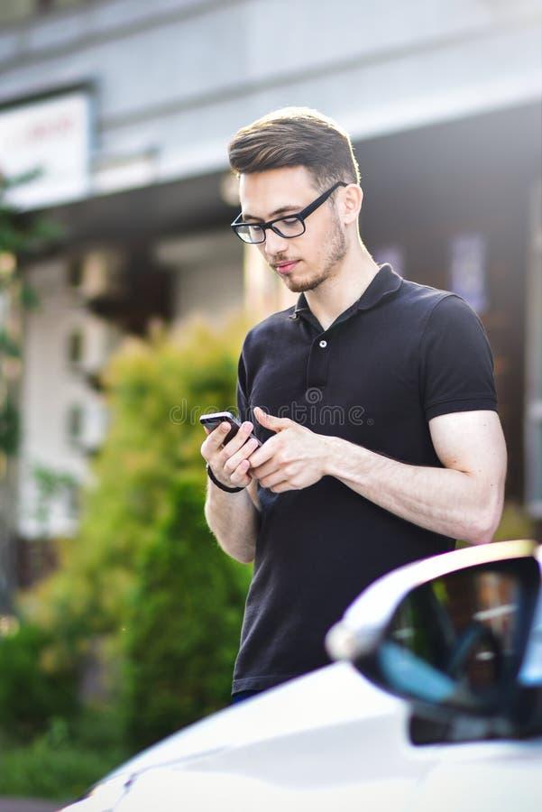 Homem novo que inclina-se em seu carro, usando um smartphone, vestido ocasionalmente imagens de stock