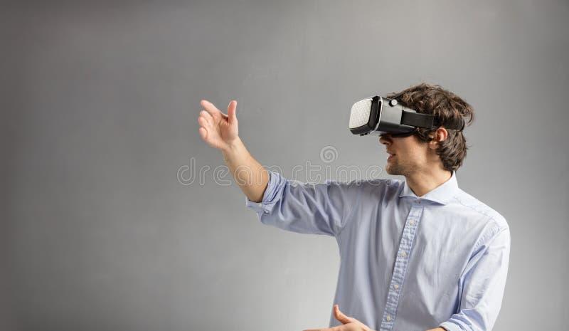 Homem novo que joga em óculos de proteção da realidade virtual imagens de stock