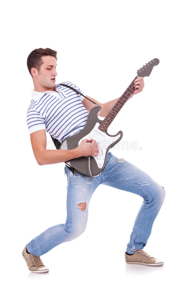 Homem novo que joga a guitarra fotografia de stock