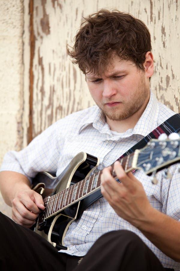 Homem novo que joga a guitarra ao ar livre imagem de stock royalty free
