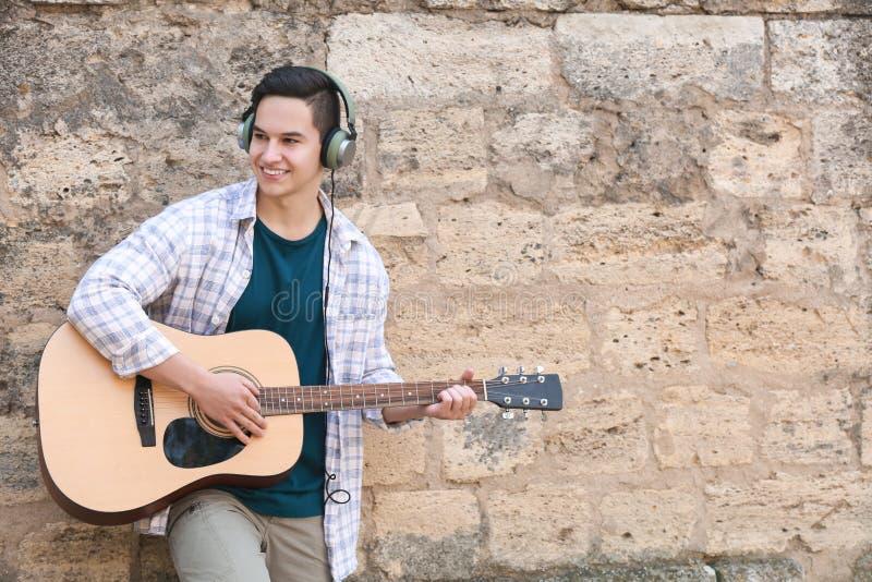 Homem novo que joga a guitarra ao ar livre fotografia de stock