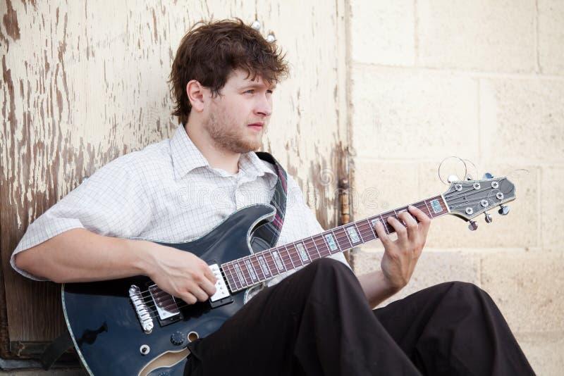 Homem novo que joga a guitarra ao ar livre fotos de stock royalty free