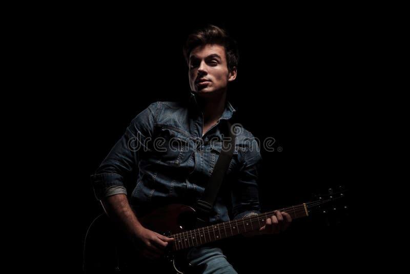 Homem novo que joga a guitarra elétrica e os olhares ao lado imagens de stock