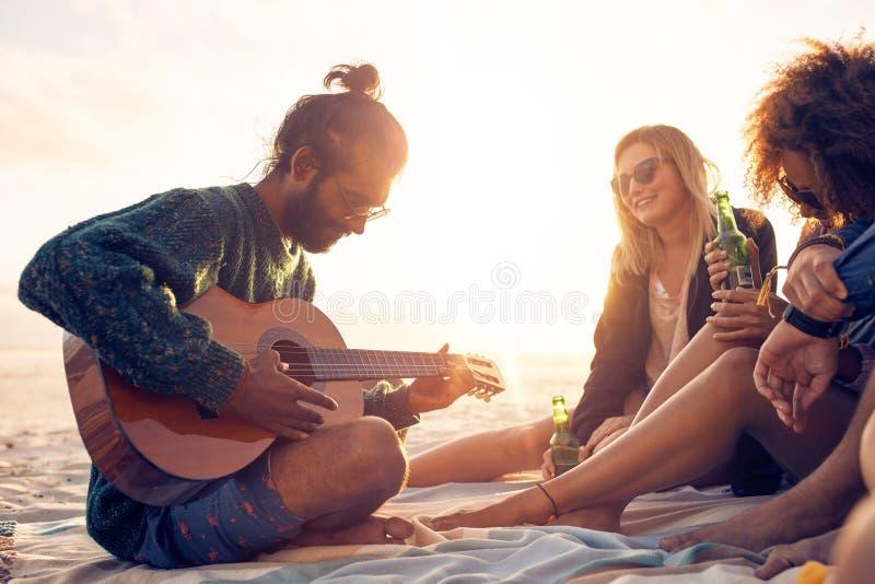 Homem novo que joga a guitarra para amigos na praia fotos de stock