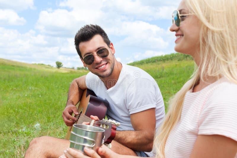 Homem novo que joga a guitarra a seus pares do dia de verão da menina fotos de stock
