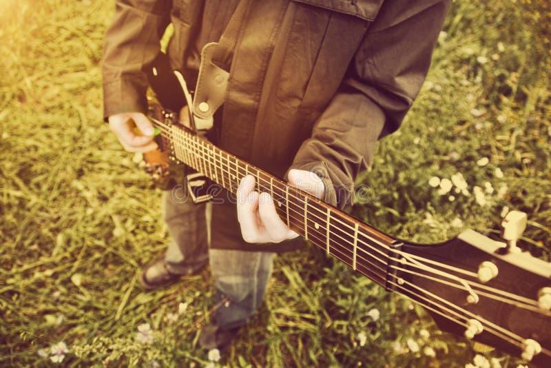 Homem novo que joga na guitarra fora imagem de stock royalty free