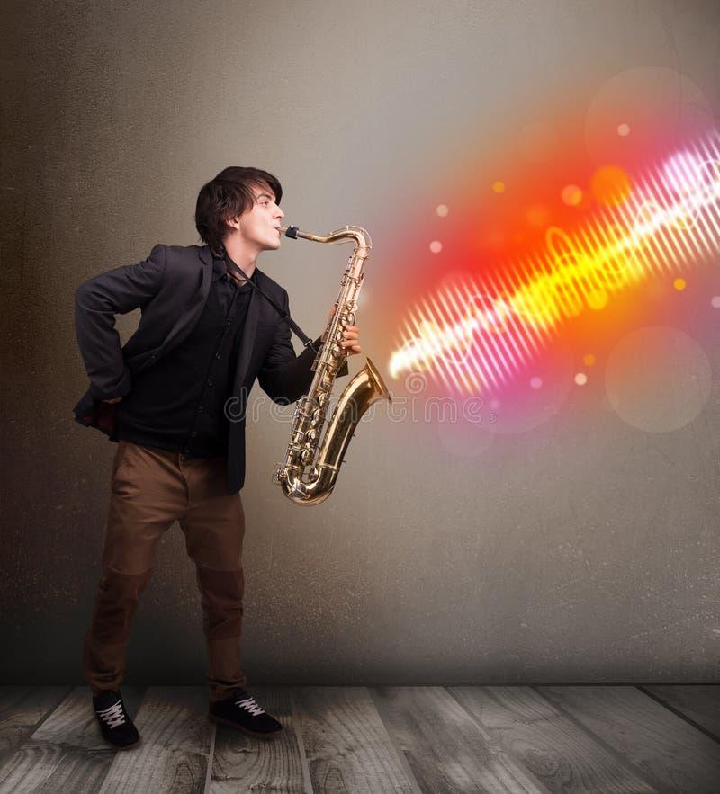 Homem novo que joga no saxofone com as ondas sadias coloridas imagem de stock