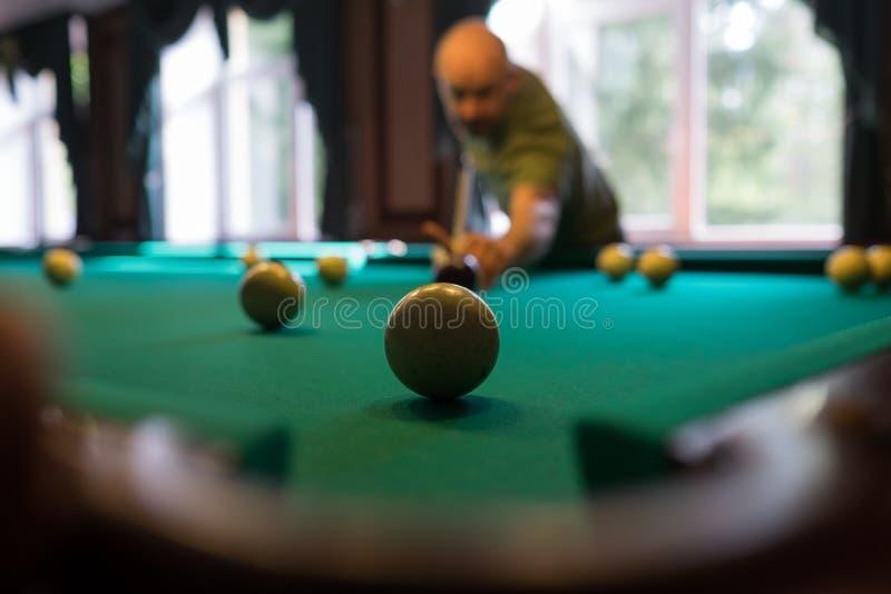 Homem novo que joga o bilhar dentro Passando o tempo livre no jogo foto de stock royalty free