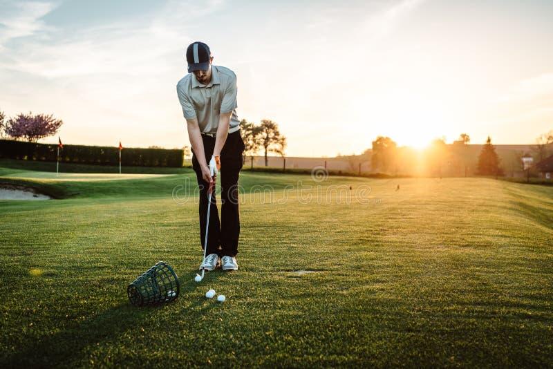 Homem novo que joga o golfe fotografia de stock royalty free
