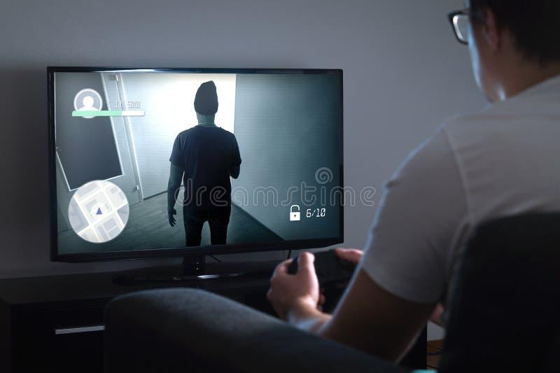 Homem novo que joga o jogo de vídeo em casa com console fotos de stock